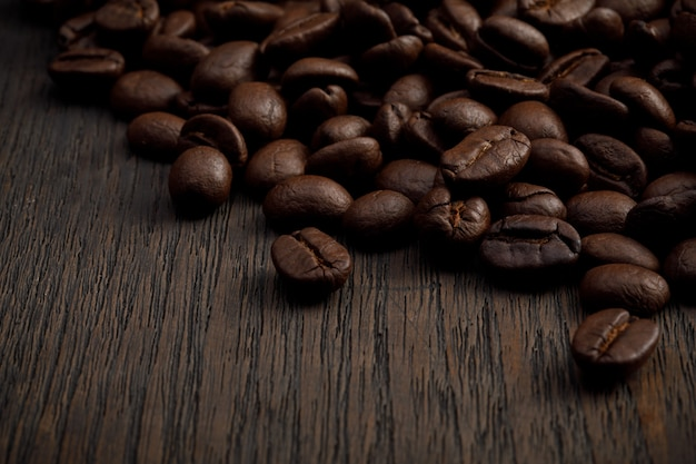 The hot of brown roasted coffee beans on brown background with copyspace