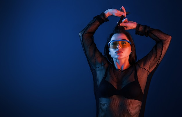 ネオン照明でスタジオでポーズをとるサングラスの熱いブルネット。