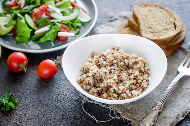 プレートに溶けるバターとテーブルの上のランチのための新鮮な野菜の健康的なベジタリアンサラダ、上面図、コピースペースの健康的な食品のコンセプトと温かいそばのお粥。ダイエットメニュー