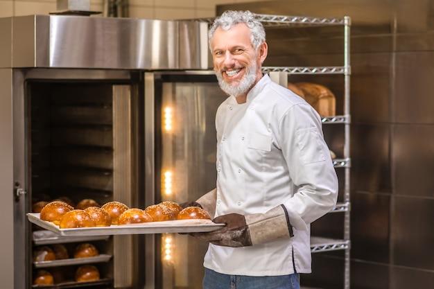 뜨거운 빵. 빵집에서 오븐 근처 갓 구운 빵 베이킹 시트와 장갑에 즐거운 회색 머리 수염 난된 남자