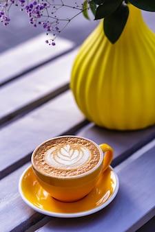 오렌지 컵에 담긴 뜨거운 카푸치노 커피, 배경에 꽃이 있는 노란색 꽃병