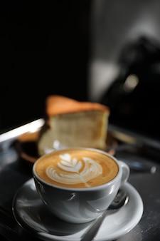 Горячий капучино или кофе латте-арт из молока на деревянном столе в кафе