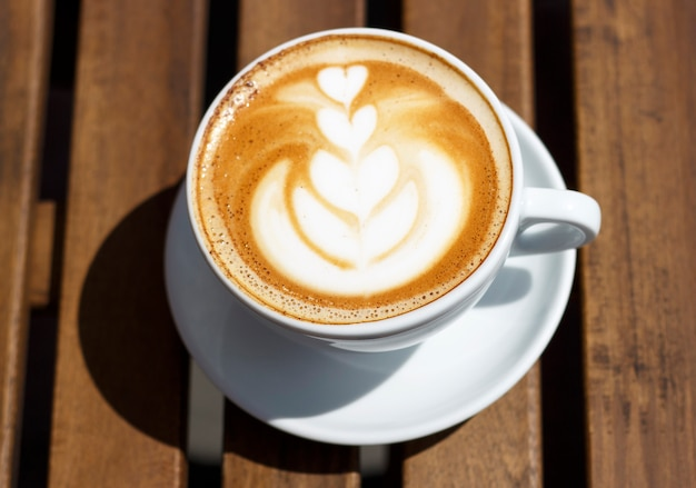 Hot cappuccino with froth and pattern on wooden table, top view