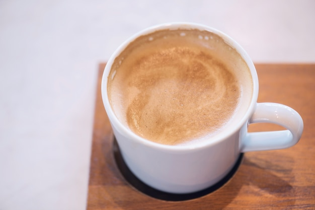 Hot cappuccino with frothy milk foam in white coffee cup on wooden plate by top view