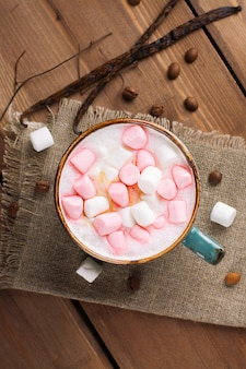 Hot cappuccino with marshmallows in a mug.