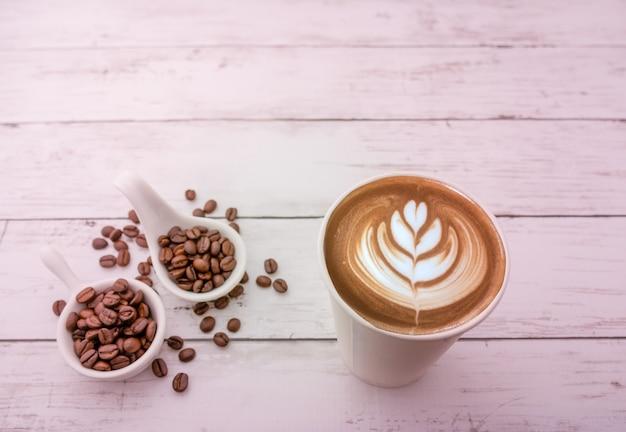 木製の背景と空きスペースにローストコーヒー豆とホットカプチーノ