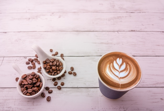 Hot cappuccino with roasted coffee beans on a wooden background and free space