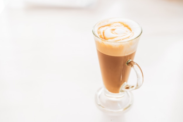 Hot caramel macchiato in a tall glass with caramel sauce on top close up.