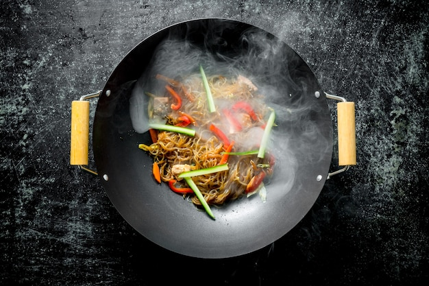 Hot cellophane noodles in a frying pan wok with bell peppers, cucumber and carrots on dark wooden table