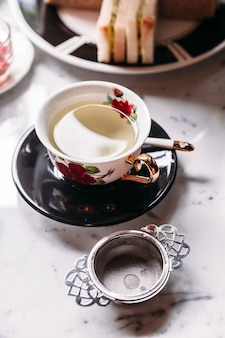 Hot chamomile tea served in porcelain vintage cup with stainless steel tea strainer infuser.