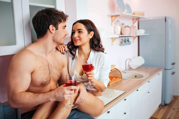 Hot cheerful couple sit on kitchen cabinet. young woman hold hands on guy's. they look at each other and smile. couple has glasses of wine in hands.