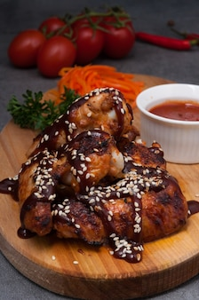 Hot chicken wings with tomato sauce on a wooden board
