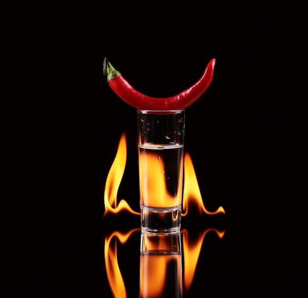 黒に火をつけたショットグラスのホットチリペッパー