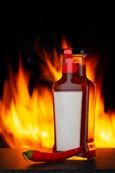 Острый перец чили соус и огонь на заднем плане