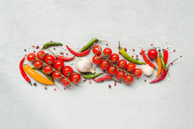 Hot chili peppers multi-colored, tomato cherry on branch