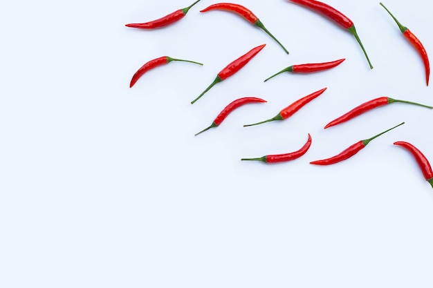 Hot chili peppers on white wall. top view