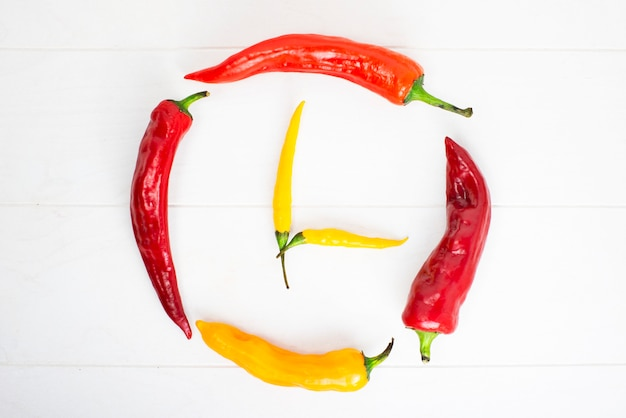 Hot chili peppers on white wooden background