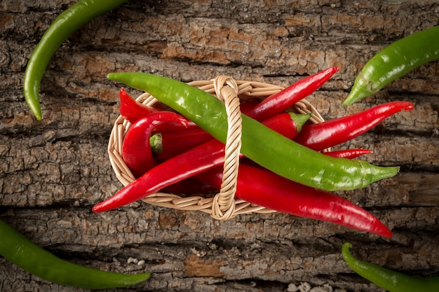 Hot chili peppers  in a wicker basket on wooden background