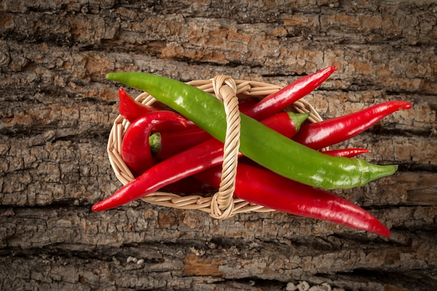 Hot chili peppers  in a wicker basket on wooden table