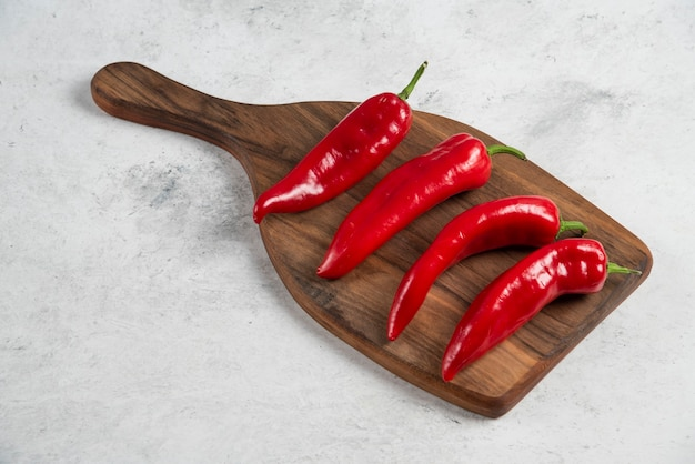 Hot chili peppers on wooden board.