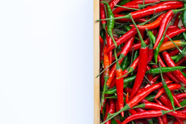 Hot chili peppers in wooden box on white surface. top view