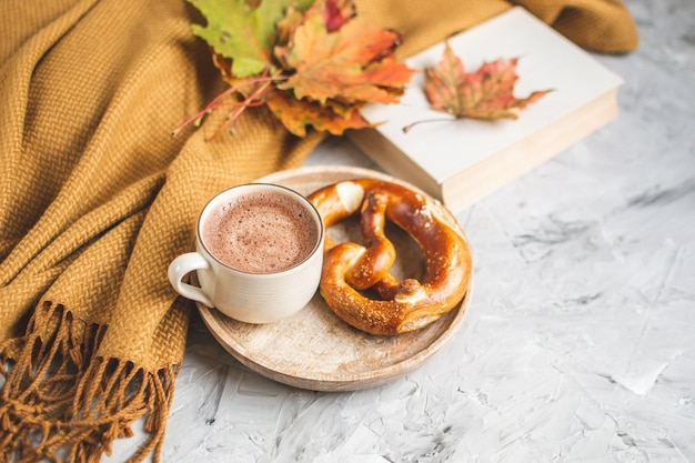 Hot chocolate autumn time bakery pretzel blanket yellow leaves gray background