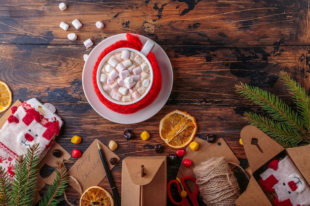 Hot chocolate cacao with marshmallows knitted hand made red cloth for a mug top view packaging gifts and presents christmas decoration