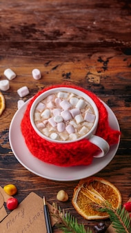 Hot chocolate cacao with marshmallows knitted hand made red cloth for a mug