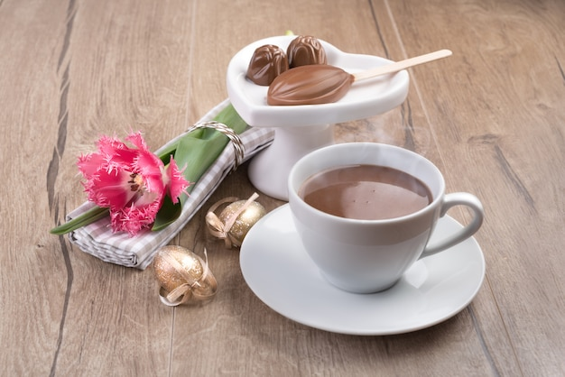 Hot chocolate and chocolate pralines on wood