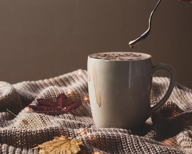 Горячий шоколадный напиток какао в большой чашке на вязальной поверхности с осенними листьями