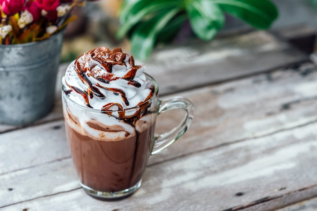 Hot chocolate cocoa in glass mug with whipped cream