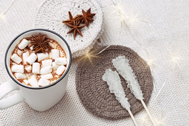 Hot chocolate or cocoa with marshmallows with cozy soft knitted fabric decorated lights.