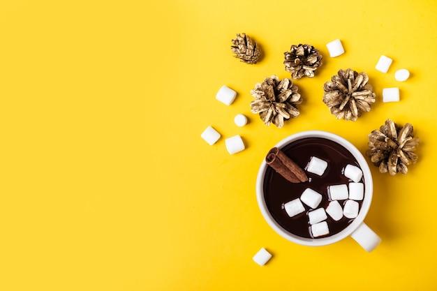 黄色の背景にシナモンとマシュマロのホットチョコレートカップ。暖かいクリスマスの冬の飲み物。