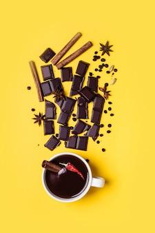 唐辛子とシナモンのホットチョコレートカップ。黄色の背景で調理するための材料。暖かい冬や秋の飲み物のコンセプト。