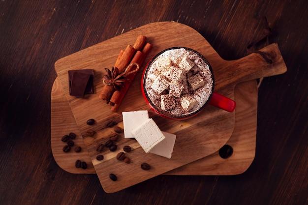 Горячий шоколад, чашка с зефиром, вид сверху, на деревянном столе, тонировка в коричневых тонах