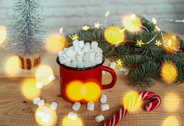 Hot chocolate cup with marshmallows with christmas lights and christmas tree branches