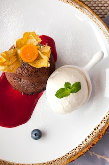 Hot chocolate fondant with ice cream on white plate