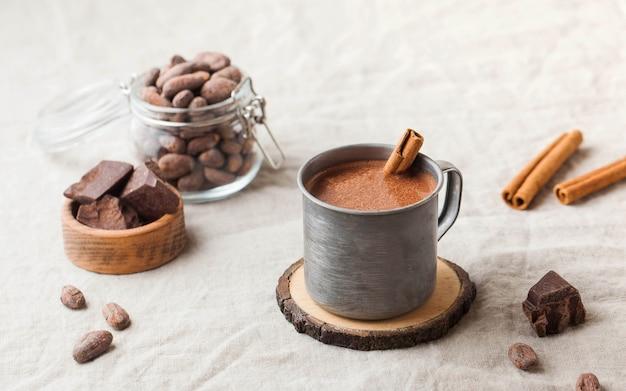 Горячий шоколад в металлической кружке с палочкой корицы на скатерти.