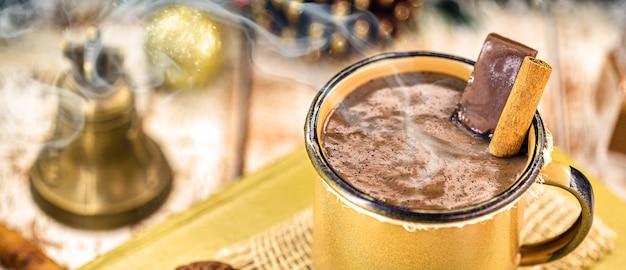 黄金の銅のマグカップのホットチョコレート、シナモン、煙または蒸気と一緒に熱いクリスマスまたは冬の飲み物。