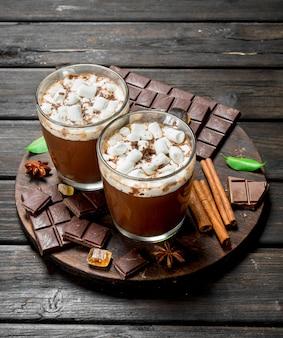 Горячий шоколад в кружках с зефиром и ароматной корицей на деревенском столе.