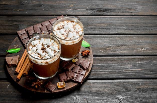 Горячий шоколад в кружках с зефиром и ароматной корицей. на деревянном столе.