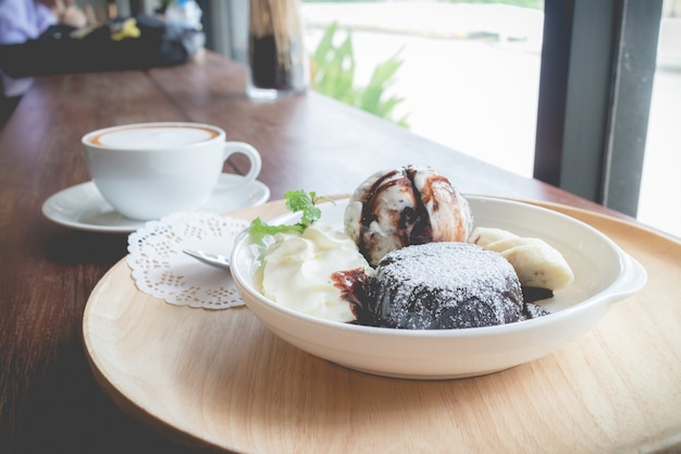 Hot chocolate lava cake with vanilla ice cream ball, banana and whipped cream