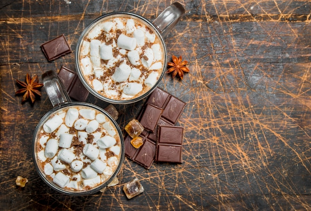 Hot chocolate in mugs with marshmallows and fragrant cinnamon. on a wooden table.