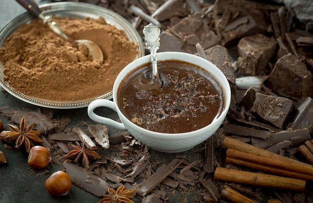 Горячий шоколад на старом фоне в композиции с какао-бобами и орехами.