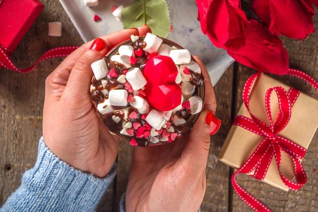 Чашка горячего шоколада или кофе латте на утро дня святого валентина. горячий шоколад или латте в стиле сумасшедшего коктейля с большим количеством зефира и сердечками, сахарной посыпкой, с подарочными коробками и цветами роз