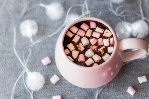 ホットチョコレートピンクのセラミックマグマシュマロとガーランドグレーのニットの背景