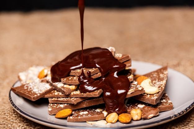 Cioccolata calda che versa sulle caramelle in tela bianca vestirono.