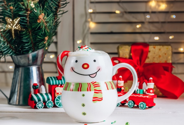 Hot chocolate in smiling snowman mug in christmas setting. selective focus