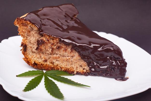Thcのホットチョコレートスポンジケーキ、プレートと緑の葉のマリファナのケーキ。