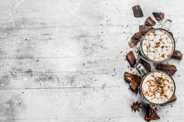 Hot chocolate with chunks of bitter chocolate and marshmallows. on a rustic table.